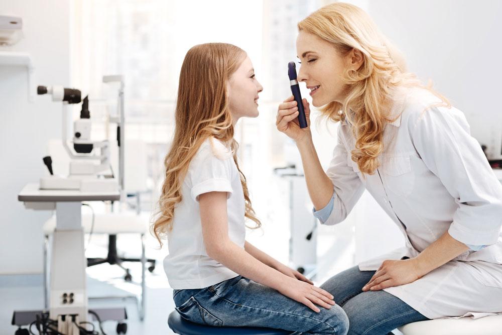 doctor examining eyes of girl