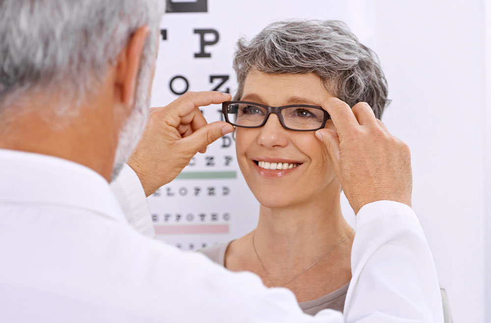 eye doctor helping woman try on glasses