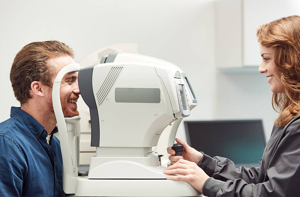 optometrist examining male patients eyes