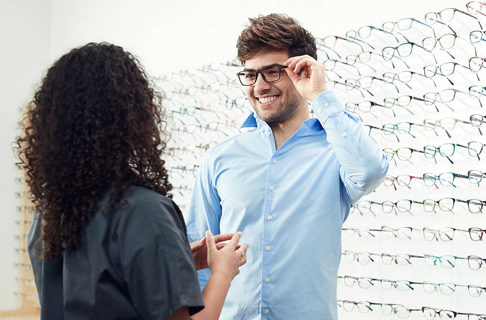 man shopping for glasses with eye doctor