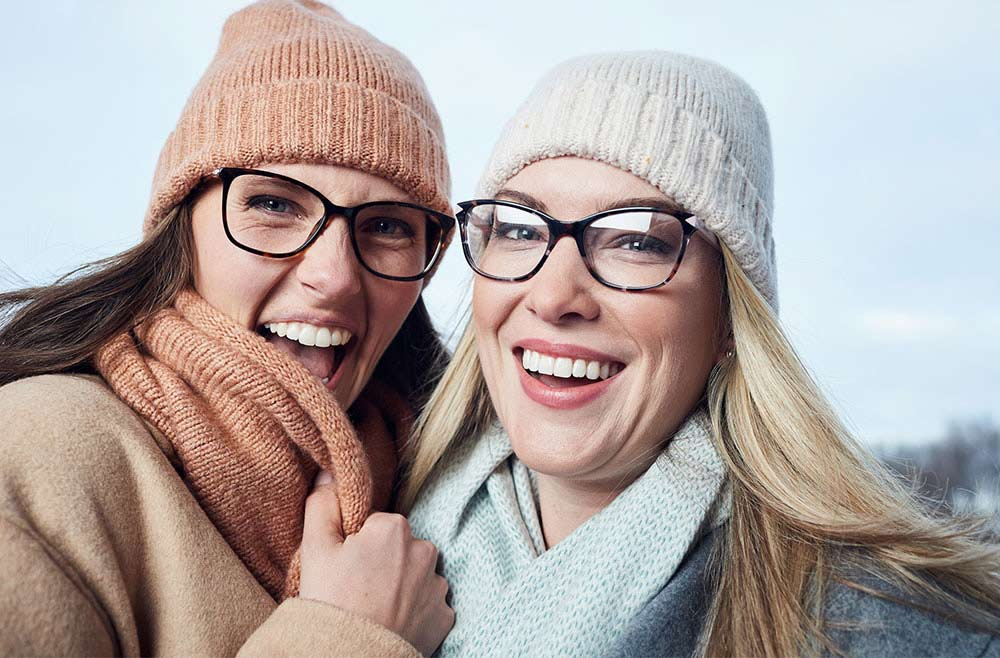 two smiling women wearing glasses