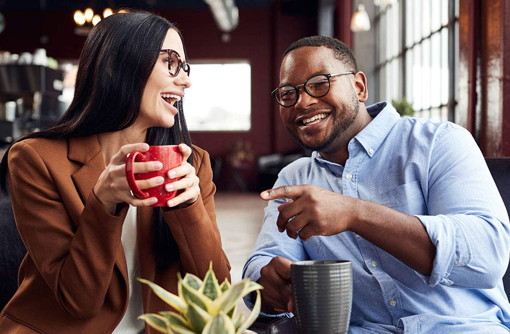 man and woman drinking coffee wearing glasses
