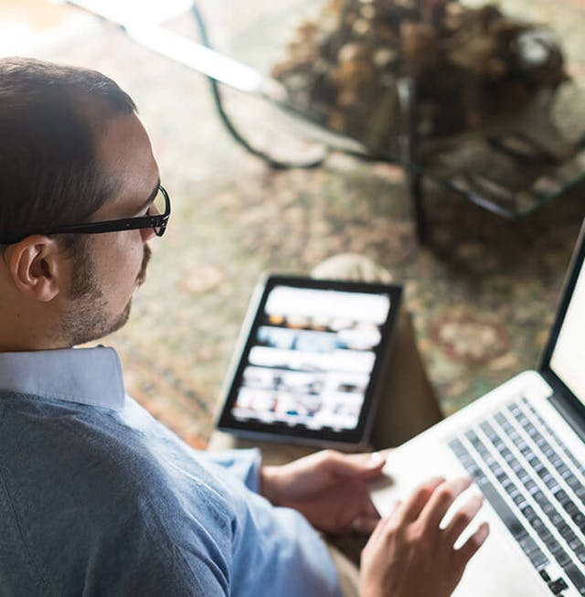 man wearing glasses working on computer