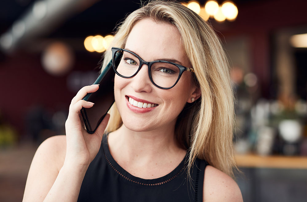 woman wearing glasses talking on the phone
