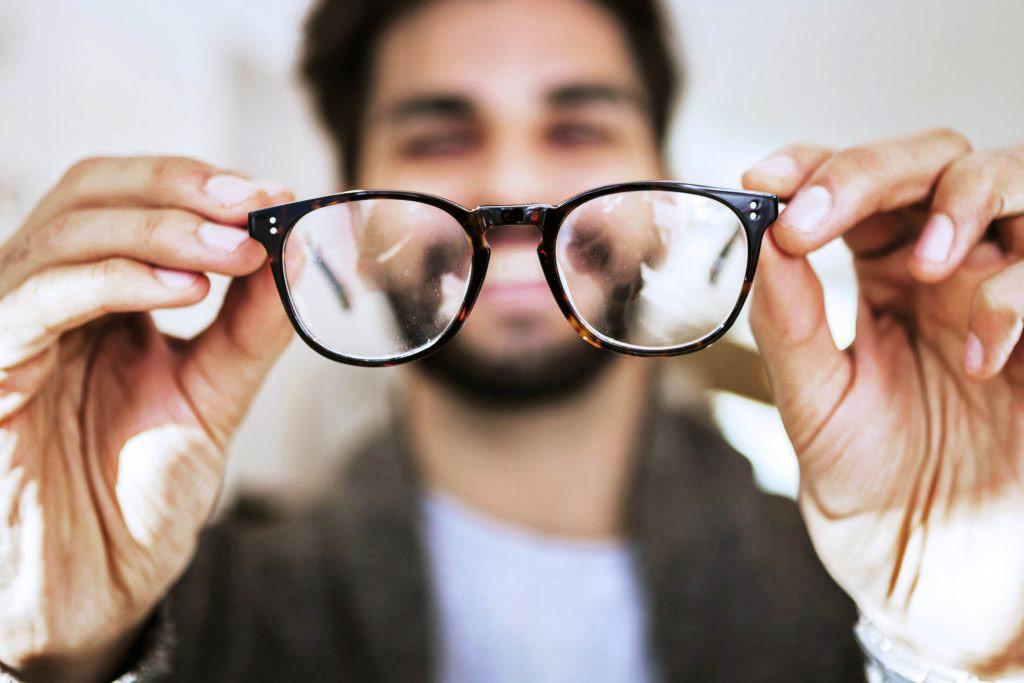 man holding eyeglass frames