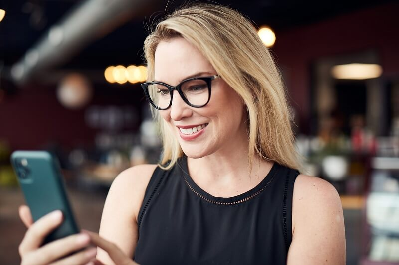 woman in coffee shop looking at cell phone